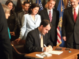 Governor Scott Walker signs Voter ID bill as Republican legislators look on.