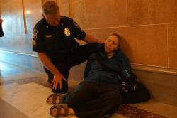 Dawn Henke in cardiac distress on the floor of the Capitol while handcuffed. Source: Leslie Amsterdam
