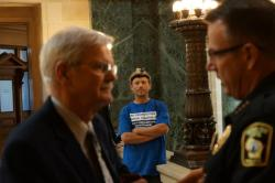 Chief David Erwin of the Capitol police talks to Senator Mark Miller about civil rights in the Capitol while Jason Louise Huberty who has received 6 citations during the recent crackdown looks on.