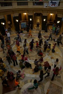 The Solidarity Forever march around the rotunda at the end of Tuesday's Solidarity Sing Along at WI Capitol swelled in numbers as a large group of school children visiting the Capitol joined in this daily tradition.  The space was shared by everyone.  Several Capitol police officers were on duty during the event.  No incidents were reported.