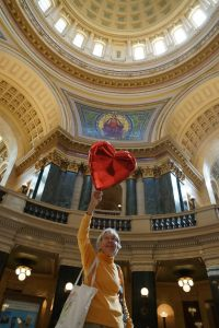 Joan Kemble holds up her red heart balloon in the rotunda of the Capitol.  An iconic symbol of the Wisconsin Uprising, heart balloons are banned in the Capitol and citizens have been arrested and ticketed $263.50 for their release into the dome. Joan did not receive a ticket as she did not let go of the balloon. Photo: Leslie Amsterdam