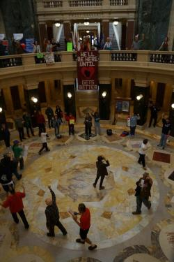 "Irving Smith, in the red t-shirt and holding a songbook on the bottom of the photo, leads the Solidarity Forever march in the rotunda during the Solidarity Sing Along on Wednesday. Irving also conducted the noon hour song circle. A Capitol police officer observes the proceedings, however no action is taken to stop the singing. Irving received a citation about an hour later as he left the Capitol for ""Obstruct Access/Passage(NO PERMIT) for his activities in the rotunda. No other citations were issued to other participants, as the Capitol Police appears to be targeting the ""leaders/conductors"" of this popular noon hour activity."