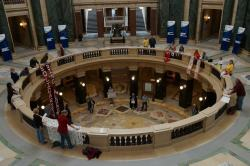 This is the scene over the noon hour on 10/8/12 at the WI Capitol.  One of the singers seen here has received a citation, home delivered by WI Capitol Police officers, for their participation in this spontaneous song circle that occurs Monday-Friday from 12-1.  Can you guess who the offender is? Can you determine what their offense was? Can you explain why only 1 of these individuals was cited for the incorrect behavior? Photo: Leslie Amsterdam