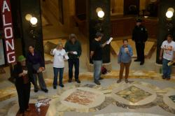 Ofc Andrew Hyatt of WI Capitol police surveys the scene and takes notes during the noon hour song circle in the Capitol. Brandon Barwick, on the left in the green fedora, later received a citation via certified mail for: Obstruct Access Passage (No Permit). Admin Code 2.14(2)(v), issued by Officer Andrew Hyatt