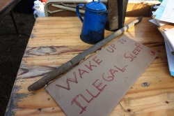 """""""Wake Up to Illegal Sleeping,"""" says the sign that desicribes the experience of Occupy Madison this morning. Photo by Rebecca Kemble"""