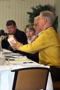 Committee members examine a carton that held drinking water distributed