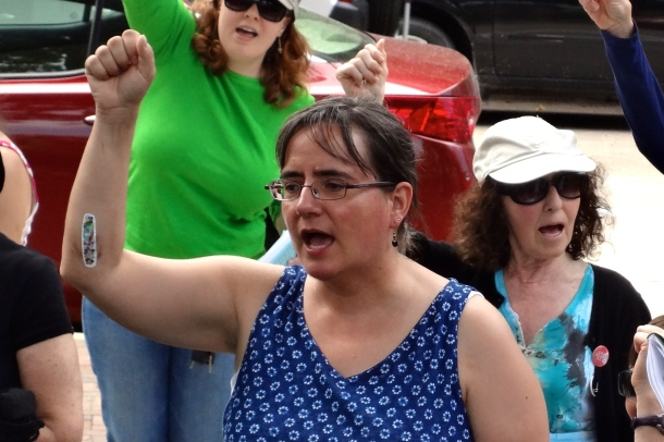 Sue Breckenridge raises her fist during the singing of Solidarity Forever at the sing along.