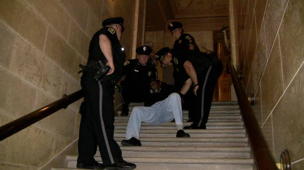 Vietnam veteran Will Williams falls on a marble staircase while handcuffed and under arrest by Capitol police. Photo by Alex Oberley
