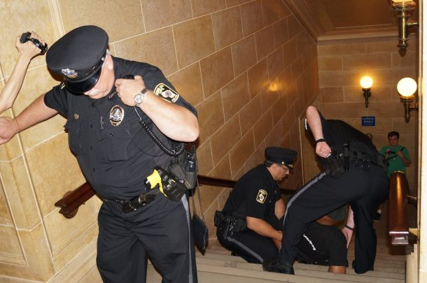 Will Williams arrested in WI Capitol 8.1.13 falls while handcuffed and under arrest in WI Capitol 8.1.13. Photo by Leslie Amsterdam