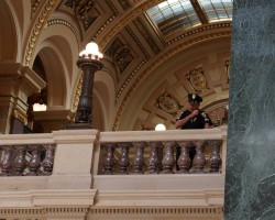 WI Capitol Police Capt Lonergan  speaks into his shoulder communications devive as he directs the arrests of peaceful singers from a second floor balcony. Photo courtesy Leslie Peterson