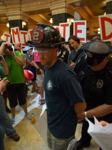 Firefighter Ted Higgins being handcuffed by Cap Police. Photo by Leslie Peterson