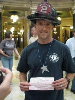 Madison firefighter Ted Higgins shows off his citation. Photo by Nicole Desautels.