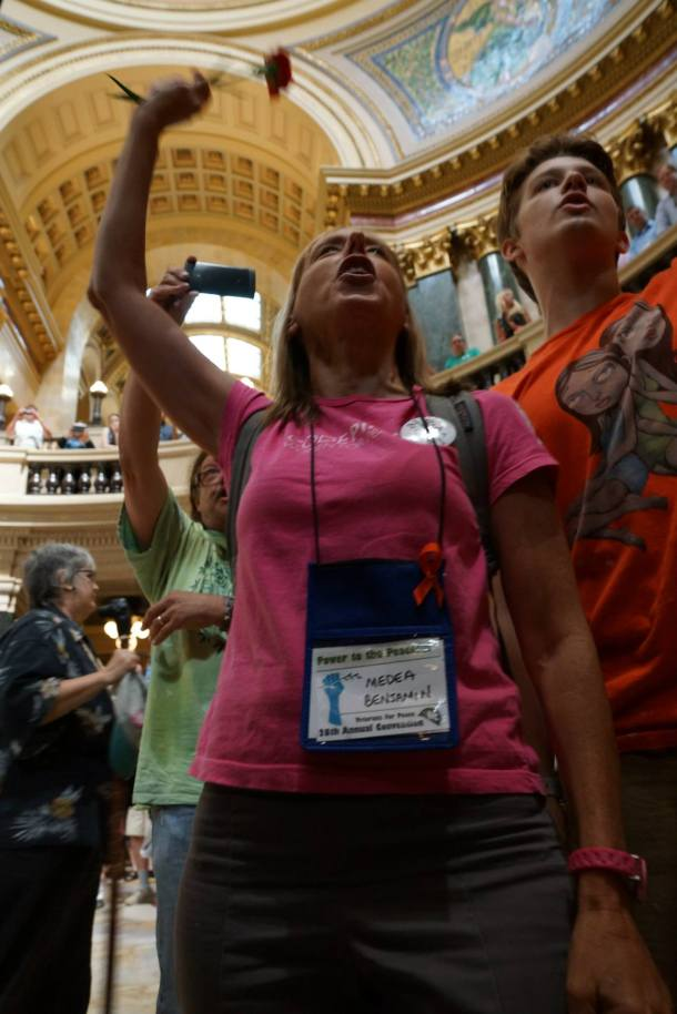 August 8, 2013 Medea Benjamin  and Jack sing immediately before jack, a minor, is arrested for singing in the WI Capitol rotunda without a permit.
