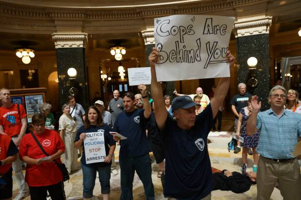 August 27, 2013 The Cops Are Behind You! Madison Cops For labor show solidarity in the rotunda the day after  a young african- amercian man was tackled and falsely arrested anf jailed while his brother was dragged off using pain compliance techniques.
