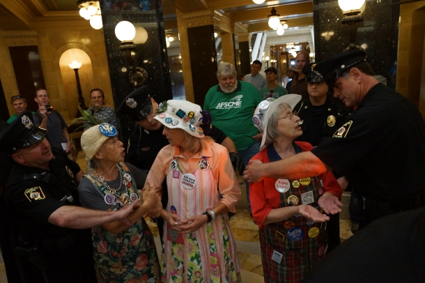 WI State Capitol Police arrest three members of the Raging Grannies of Madison for singing in the Capitol rotunda without a permit in August 2013.