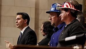 Larry Youngs, Iron County Board Supervisor and Mining Impact Committee member can be seen next to Walker in the decorated hard hat with other locals in the picture on the right.